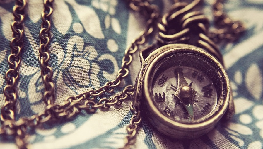 brass compass on patterned background